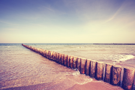 toned: Vintage toned wooden breakwater on a beach.