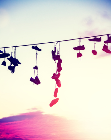 Vintage toned silhouettes of shoes hanging on cable at sunset, teenage rebellion concept.