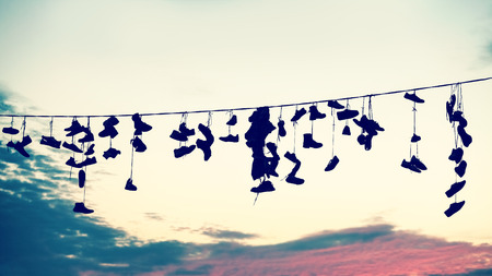 rebellion: Retro stylized silhouettes of shoes hanging on cable at sunset, teenage rebellion concept.