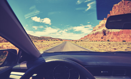Vintage toned photo of a road taken from the front seat of a car, travel concept, USA.