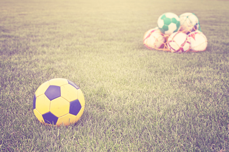 filtered: Retro filtered soccer balls on grass.