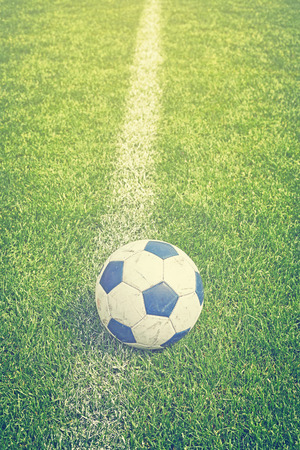 sideline: Retro toned picture of a used soccer ball on grass by sideline, shallow depth of field.