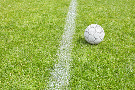 sideline: Used soccer ball on grass by a sideline, space for text, shallow depth of field.