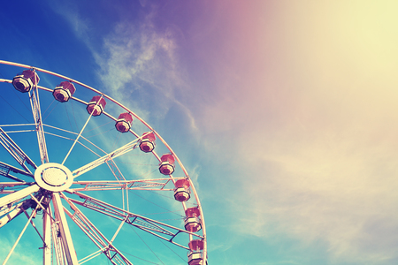 Vintage stylized ferris wheel at sunset, space for text.
