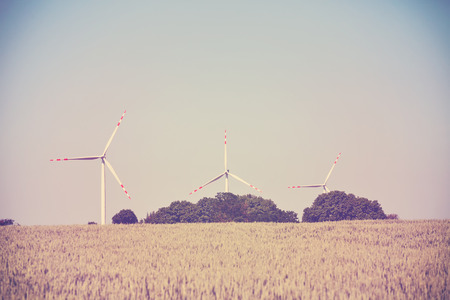 energies: Old film retro toned windmills on a cereal field, alternative energy concept.