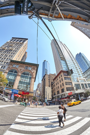 ave: New York, USA - August 15, 2015: Fisheye lens picture of pedestrian crossing at busy Fifth Ave and East 33rd St corner.