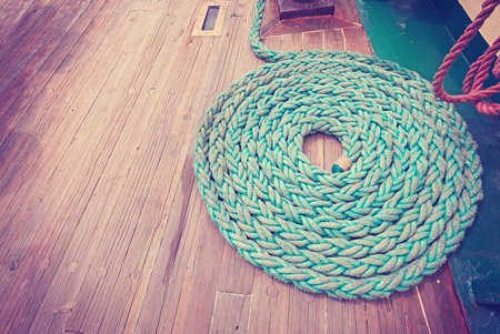 ''wide angle'': Vintage toned wide angle picture of mooring rope on wooden deck of a sailboat.