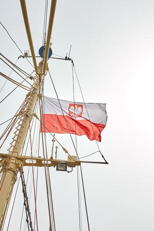 flagpole: Polish flag on a sailing ship flagpole.