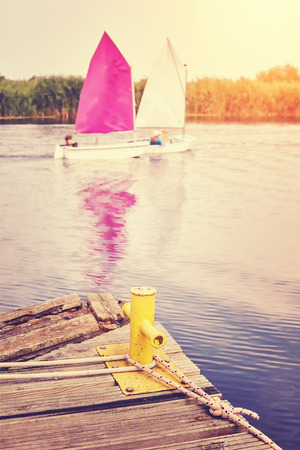mooring bollard: Vintage toned yellow mooring bollard on old wooden pier with sailboats in distance. Stock Photo