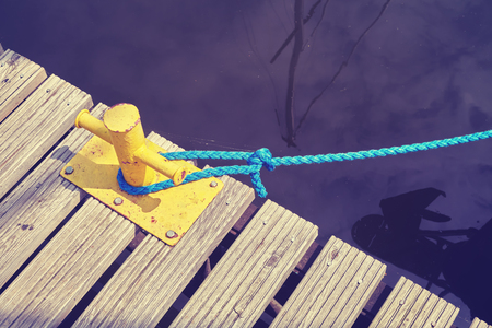 Vintage toned yellow mooring bollard with blue rope in marina, conceptual picture.