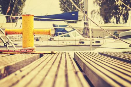 mooring bollard: Vintage toned yellow mooring bollard in marina, nautical background.