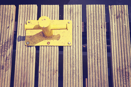 mooring bollard: Vintage toned old yellow mooring bollard on wooden pier.