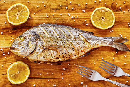 gilt head: Roasted gilt head bream fish on a wooden table with lemons and coarse grained salt.