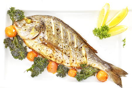 gilt head: Roasted gilt head bream fish on a white plate with grilled tomatoes, kale and coarse grained salt. Stock Photo