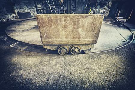 mining equipment: Retro toned old rusty mine cart, obsolete mining equipment. Stock Photo
