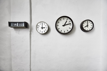 time passing: Clocks on a white wall, time passing concept, space for text.