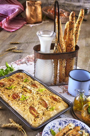 focaccia: Traditional focaccia with tomatoes and bread sticks, rustic setting on a wooden table.