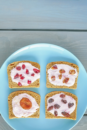 frutas secas: Bread with strawberry cream cheese and dry fruits on blue plate, healthy breakfast setting from above.