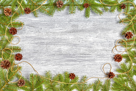 Christmas background, spruce branches frame with pine cones on a rustic wooden table, top view with copy space.