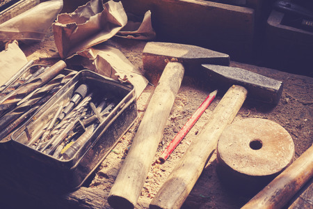 Retro toned old tools on dusty wooden table in a joinery.