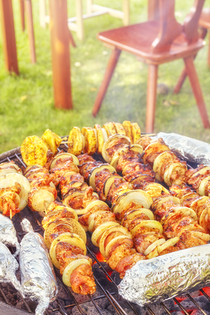 meat skewers: Meat skewers with onions and corn cobs in aluminum foil, garden barbecue, selective focus.