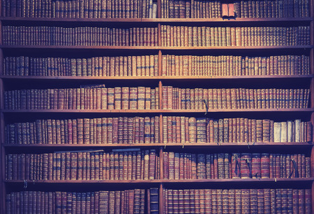 Vintage toned old books on wooden shelves, wisdom concept background. Stock Photo