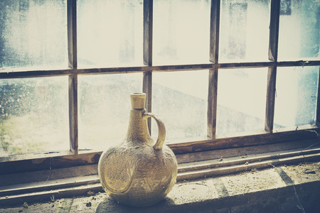 filtered: Retro filtered an old dusty clay bottle by a window.