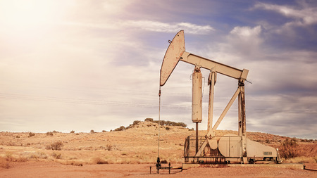Retro toned panoramic picture of an oil pump, old industrial equipment on arid soil.