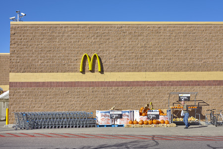 mcdonalds: Denver, USA - October 16, 2016: Unidentified man leaving Walmart store, visible McDonalds logo and decorative pumpkins Halloween sale. Editorial