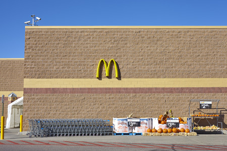 Denver, USA - October 16, 2016: Walmart store exterior with McDonalds logo and decorative pumpkins Halloween sale.