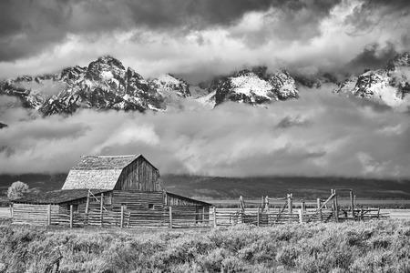 Black and white Teton mountain range with Moulton Barn in the Grand Teton National Park, Wyoming, USA.