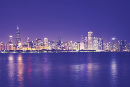 Vintage toned picture of Chicago city skyline with reflection in Lake Michigan at night, USA.