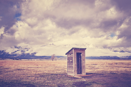 Vintage toned old wooden backcountry toilet in the Grand Teton National Park, Wyoming, USA.
