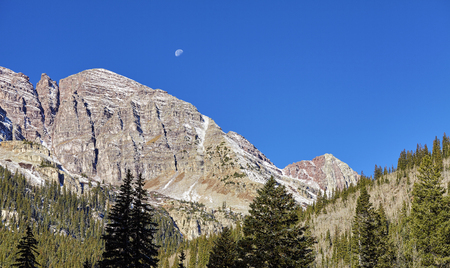 Maroon Bells mountain range with moon above, Aspen in Colorado, USA.