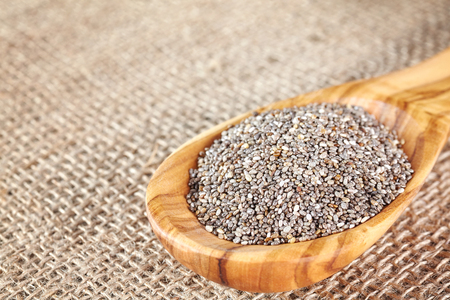 Close up picture of Chia seeds in a wooden spoon, selective focus.