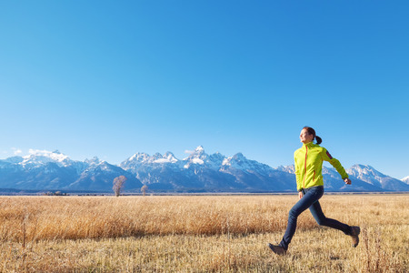 Happy young woman runs on a meadow at sunset, Grand Teton mountain range in distance, Grand Teton National Park, Wyoming, USA.