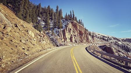 Retro color toned scenic mountain road, travel concept, Colorado, USA. Stock Photo