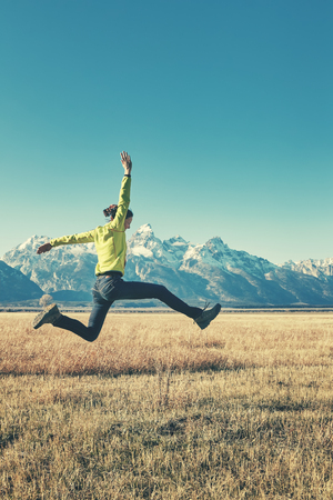 Retro stylized picture of a happy young woman jumping on a mountain meadow, Grand Teton National Park, Wyoming, USA.
