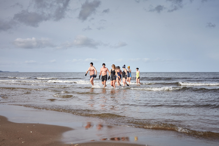 Swinoujscie, Poland - February 25, 2017: Fans of winter swimming go out from the water. Winter swimming contributes to better well being, reduces stress and fatigue, relieves pain.