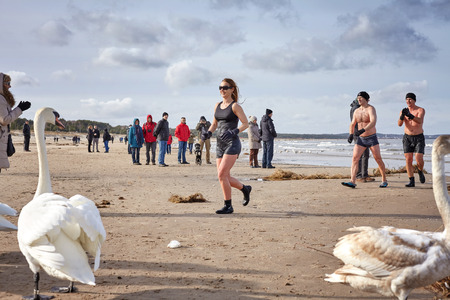 Swinoujscie, Poland - February 25, 2017: Fans of winter swimming run to warm up on the beach. Winter swimming contributes to better well being, reduces stress and fatigue, relieves pain.