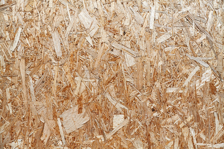 An old oriented strand board (OSB), fiberboard background of texture.