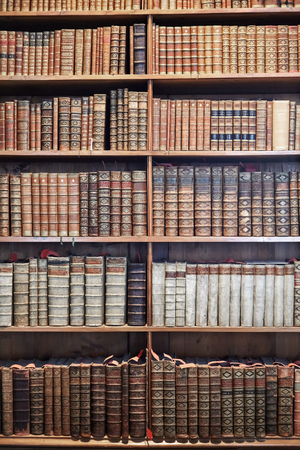 old items: VIENNA, AUSTRIA - AUGUST 14, 2016: Old books on wooden shelves in The State Hall (Prunksaal), the heart of the Austrian National Library, biggest Baroque library in Europe with 7.4 million items.