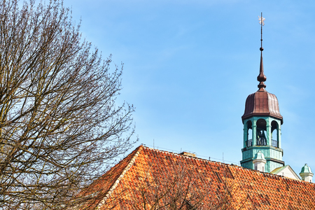 Castle belfry behind an old ceramic tile roof in Szczecin, Poland.