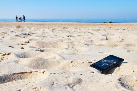 Teléfono móvil con pantalla rota en la arena en una playa, enfoque selectivo.