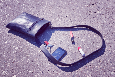 Handbag, cellular phone with broken screen, keys and lipstick on asphalt street, conceptual picture, color toning applied. Imagens