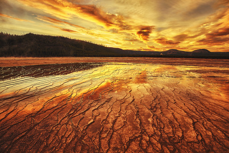 Dramatic sunset at Grand Prismatic Spring in Yellowstone National Park, Wyoming, USA.