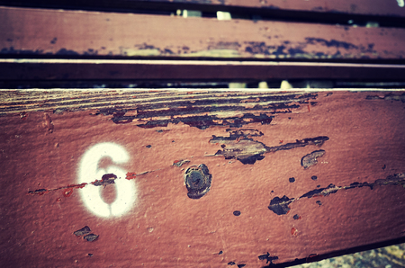 Number six painted on an old wooden seat, conceptual picture with copy space on the right. Stock Photo