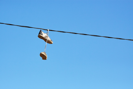 Pair of old shoes hanging on power line against blue sky, space for text.