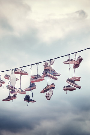 Old shoes hang on wire, color toning applied. Stock Photo