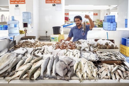 Ajman, United Arab Emirates - May 03, 2017: Man sells seafood at the local fish market.